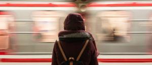 Ein Mensch mit Rucksack und Winterjacke ist von hinten zu sehen, vor ihm fährt ein ICE vorbei.
