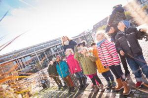 Eine Kindergruppe steht mit Erzieherin auf dem Marktplatz und schaut in den hellen Himmel zum Brüder Grimm Denkmal.