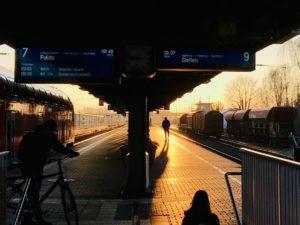 Silouetten von Personen stehen im Sonnenuntergang auf einem Bahnhgleis am Hauptbahnhof Hanau. Zu sehen Sind zwei Anzeigetafeln mit eintreffenden oder abfahrenden Zügen.