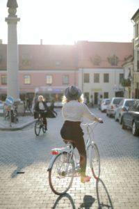 Eine Radfahrerin fährt auf Kopfsteinpflaster an parkenden Autos vorbei, im Hintergrund sind Häuser zu sehen.