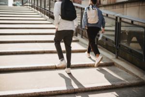 Zwei Menschen laufen eine flache Treppe hoch.