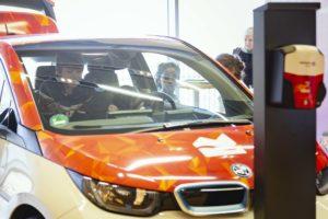 Kinder spielen auf einer Messe in einem Elektro-Auto. Ein Kind steht an der Tür weitere sitzen im Inneren des Fahrzeuges.
