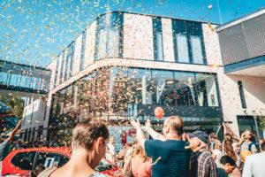 Menschenmenge wirft vor dem neu gebauten Einkaufszentrum Forum Hanau Konfetti in die Luft.