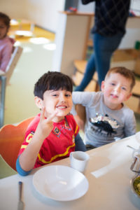 Zwei Kinder sitzen am Tisch und schauen grinsend nach oben in die Kamera.
