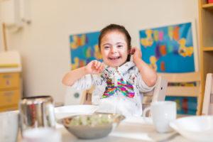 Ein Mädchen mit Down-Syndrom sitzt lachend an einem Tisch.