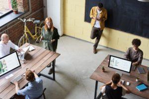 Klassenraum mit erwachsenen Menschen, von denen einer in gelber Jacke an der Tafel lehnt.