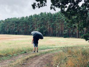 Ein Mann steht auf einer Wiese vor dem Wald und hat einen schwarzen Regenschirm aufgespannt.