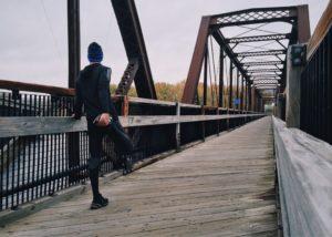 Ein Läufer in dunkler Sportkleidung steht auf einer eisernen Fußgängerbrücke und dehnt sich.