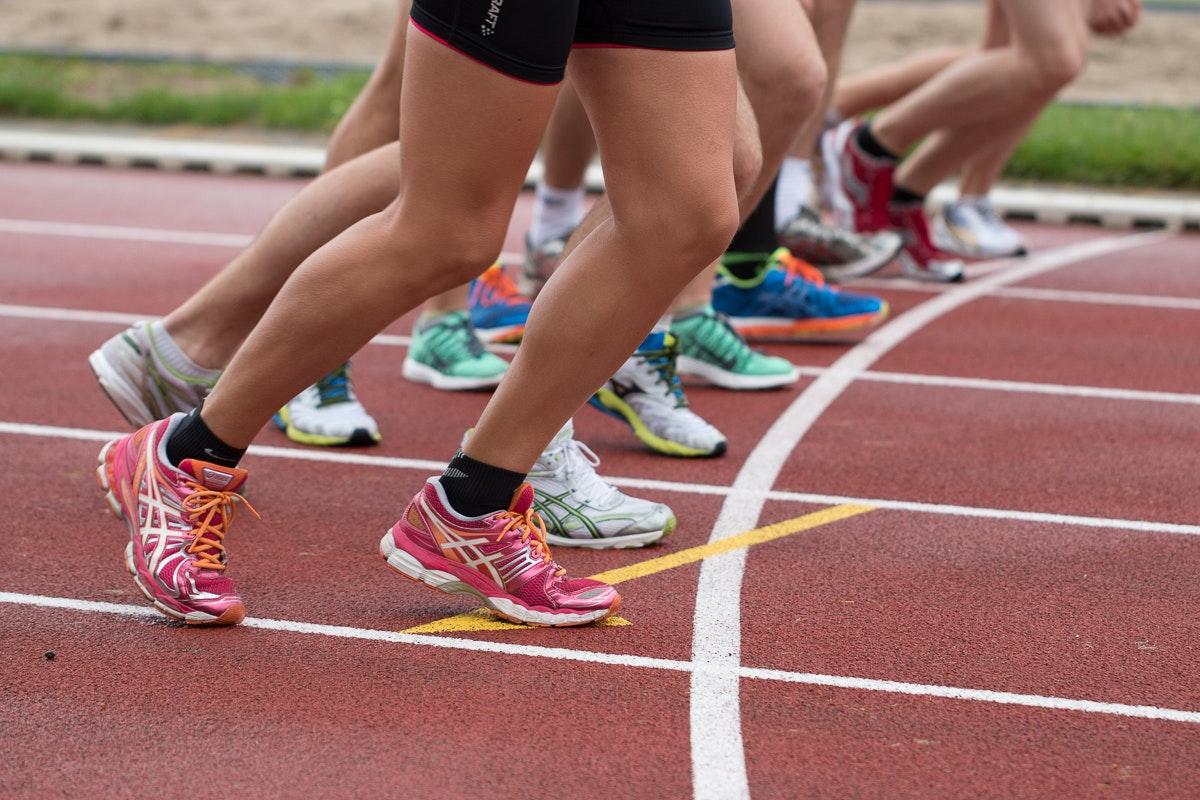 Startlinie auf der roten Rennbahn eines Sportplatzes, an der gerade Läufer starten. Zu sehen sind nur die Beine und die bunten Laufschuhe auf dem roten Bodenbelag.