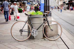 Ein Rennrad lehnt an ein bepflanztes Fass, im Hintergrund sind Menschen auf dem Bürgersteig zu sehen.