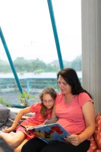 Eine Frau sitzt mit einem Kind am Fenster und lesen gemeinsam ein Buch.
