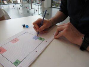 Auf einem Tisch liegt ein Block mit farbigen Feldern, eine Hand mit Stift arbeitet darauf.