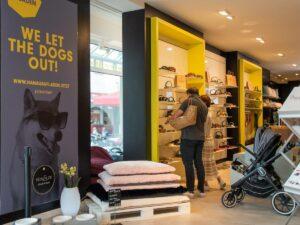 Ladengeschäft mit gelb-grauen Regalen vor denen eine Person steht.