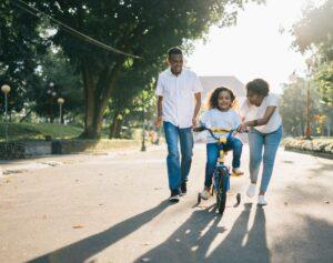 Ein Mädchen lernt Fahrradfahren, die Eltern begleiten es jeweils auf einer Seite.